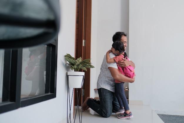 Ritratto di padre asiatico felice che accoglie suo figlio dopo aver terminato la scuola