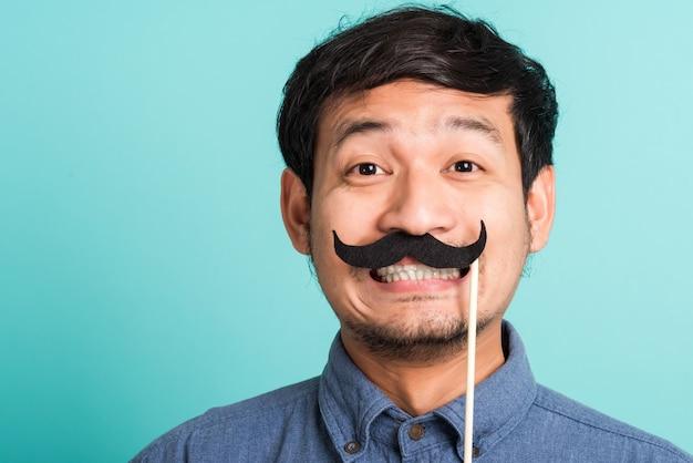 Uomo bello felice asiatico del ritratto che propone che tiene una carta divertente dei baffi o baffi falsi dell'annata sulla sua bocca
