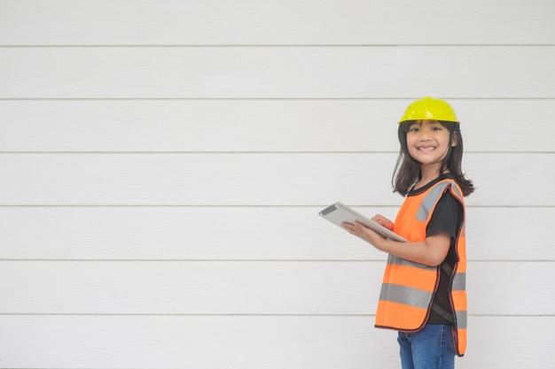 Ritratto di una bambina asiatica che indossa una maglietta riflettente e un disco di sicurezza con elmetto su tablet. per imparare e favorire lo sviluppo, piccolo architetto.