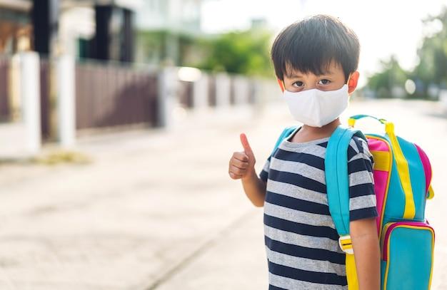 Ritratto di un ragazzino asiatico asiatico che indossa una maschera di sicurezza protettiva in quarantena per il coronavirus con allontanamento sociale pronto a tornare a scuola dopo il covid-19 con lo zaino. ritorno al concetto di scuola