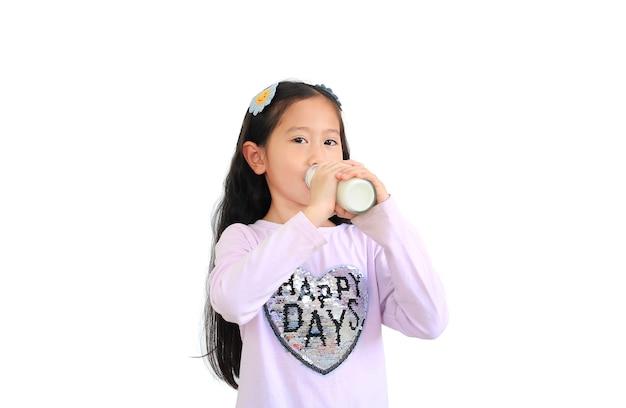 Ritratto della ragazza asiatica del piccolo bambino che beve latte dalla bottiglia di vetro isolata su bianco