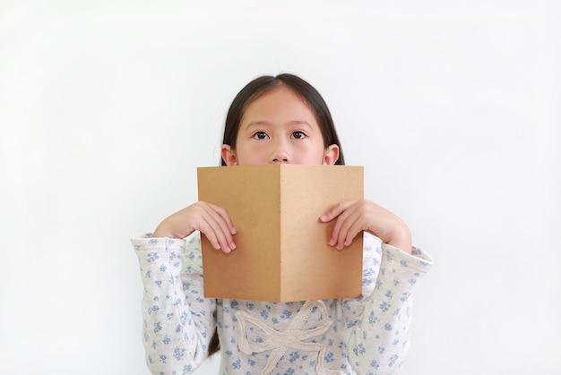 Ritratto di una bambina asiatica che tiene in mano un libro marrone aperto che si copre la bocca con lo sguardo su sfondo bianco