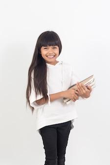 Ritratto di bambina asiatica con libri isolati