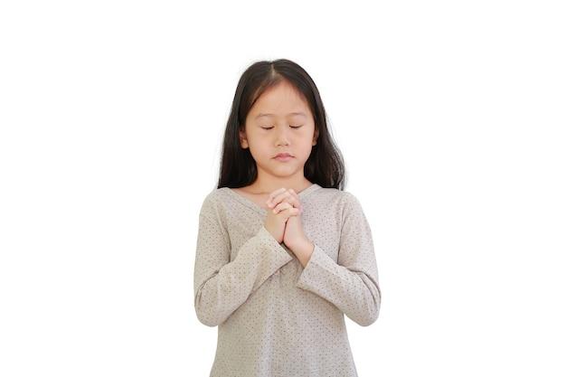 Ritratto della bambina asiatica che prega gesto isolato su priorità bassa bianca