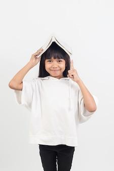 Il ritratto della bambina asiatica ha messo il libro sulla testa.