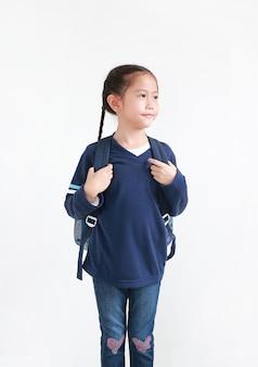 Ragazza asiatica del bambino del ritratto in uniforme scolastica casuale con lo zaino isolato su bianco