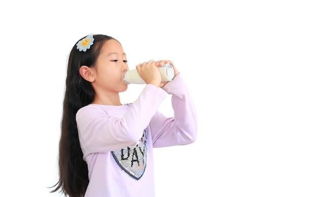 Ritratto della bambina asiatica del bambino che beve latte dalla bottiglia di vetro isolata su fondo bianco