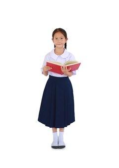 Ritratto di piccola studentessa asiatica in uniforme scolastica tailandese in piedi con un libro di testo aperto in mano isolato su sfondo bianco. a tutta lunghezza con tracciato di ritaglio.