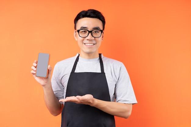 Ritratto di cameriere maschio asiatico in posa sulla parete arancione