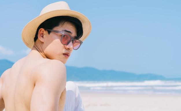 Ritratto di uomo asiatico sulla spiaggia