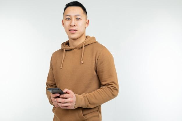 Ritratto di un uomo asiatico in una felpa con cappuccio casual con uno smartphone in mano su un bianco