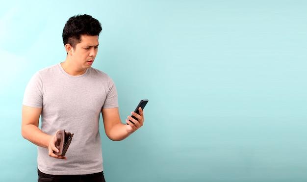 Ritratto di uomo asiatico con cellulare un scioccato, sorpreso senza parole. in possesso di un portafoglio vuoto sul muro blu.
