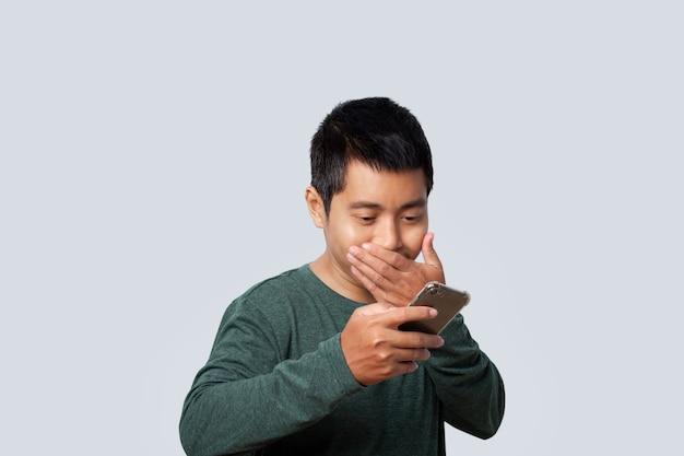 Il ritratto dell'uomo asiatico che utilizza lo smartphone ha sorpreso le notizie isolate su fondo grigio.