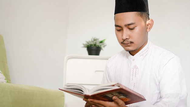 Ritratto di uomo musulmano asiatico che legge il sacro corano a casa