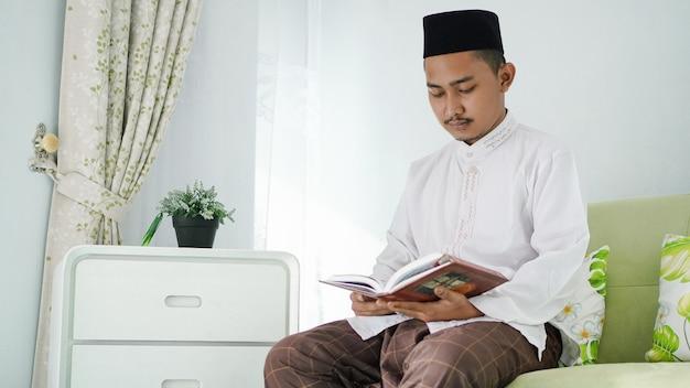 Ritratto di uomo musulmano asiatico seduto sul divano a leggere il corano a casa