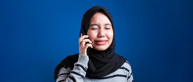 Il ritratto della donna musulmana asiatica riceve cattive notizie al telefono, espressione di pianto triste. su sfondo blu