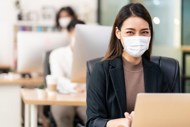 Il ritratto della donna di affari dell'impiegato di ufficio asiatico indossa la maschera protettiva per il lavoro nel nuovo ufficio normale