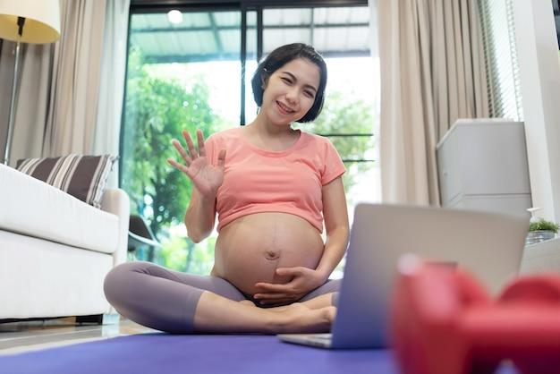 Ritratto della donna incinta asiatica che fa video chat online sul computer portatile a casa.