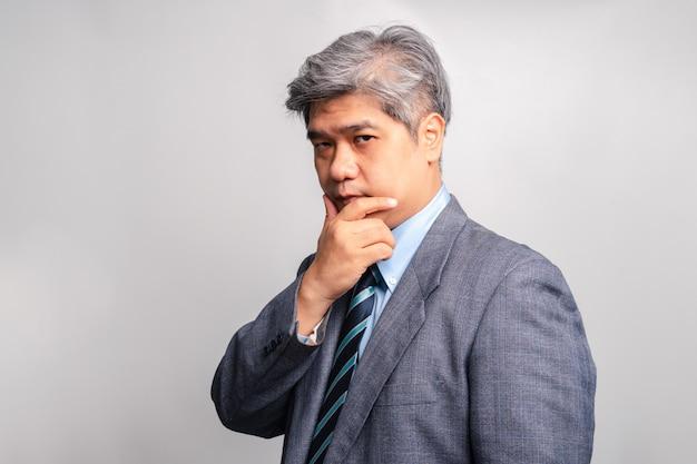 Il ritratto dell'uomo d'affari senior asiatico in vestito sta pensando su fondo bianco (sfondo isolato). il concetto di gestione e pianificazione per il successo di un'impresa