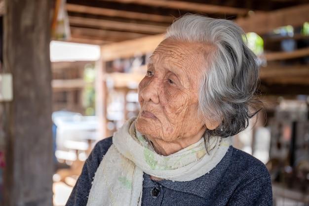 Ritratto di donne anziane asiatiche, donna anziana con capelli grigi corti seduto a casa nella campagna della thailandia