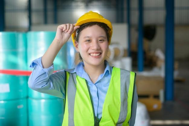 Ritratto di una donna di ingegneria asiatica sorridente sta lavorando in un moderno magazzino