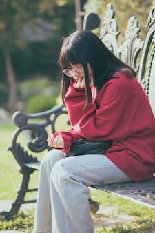 Ritratto di adolescente asiatico indossando occhiali da vista seduto sulla panchina