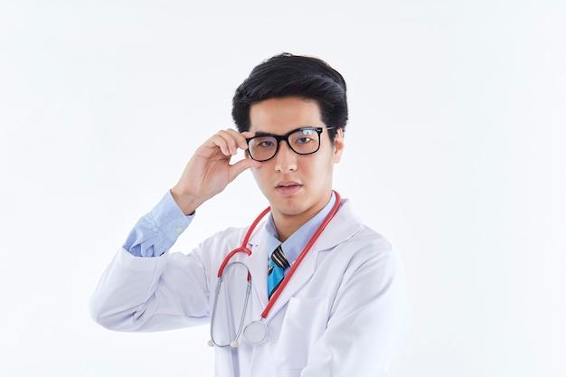 Medico maschio medico tailandese asiatico del ritratto sul muro bianco