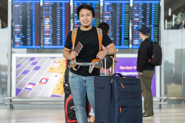 Ritratto di viaggiatore asiatico con bagagli con passaporto in piedi sul bordo di volo per c