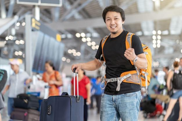 Ritratto del viaggiatore asiatico con i bagagli con il passaporto che controlla il bordo di volo