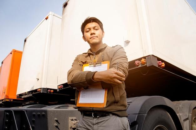 Ritratto dell'autista di camion asiatico che sta con un rimorchio del camion. lista di controllo di manutenzione del veicolo di sicurezza di ispezione