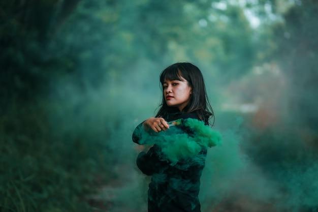 Ritratto della donna asiatica in panno nero con il fumo del fuoco di colore nel concetto della strega della foresta