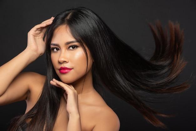 Ritratto di donna asiatica svolazzanti gettare i capelli in aria per la campagna pubblicitaria di shampoo, sfocatura sui capelli come movimento