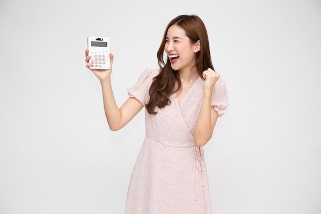 Ritratto di donna asiatica che tiene calcolatrice isolata su sfondo bianco