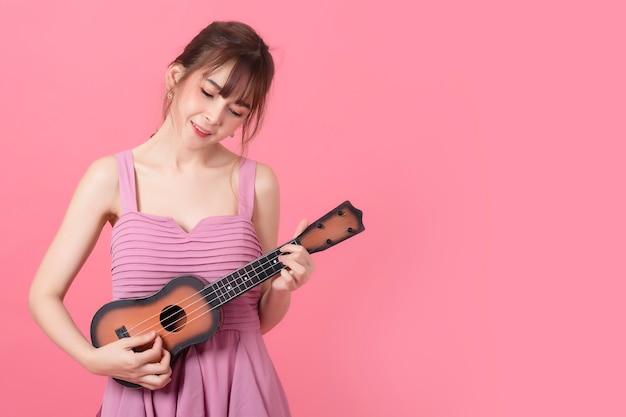 Ritratto di donna asiatica capelli lunghi che indossa un abito rosa gioca ukulele isolare sul rosa