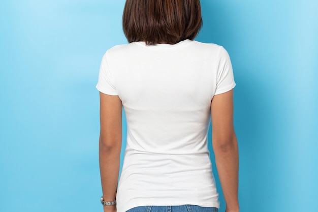 Ritratto della donna asiatica in maglietta bianca in bianco del modello su fondo blu