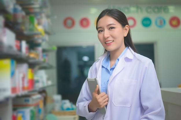 Un ritratto di donna asiatica farmacista utilizzando tablet in una moderna farmacia farmacia