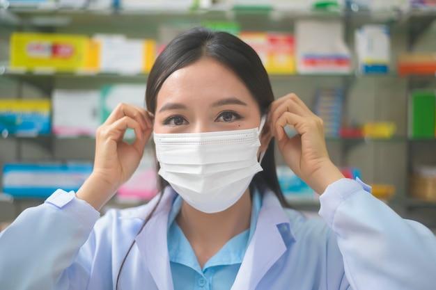 Un ritratto del farmacista asiatico della donna che indossa una mascherina chirurgica in una farmacia moderna della farmacia