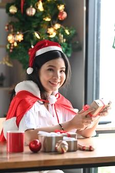 Ritratto di donna asiatica con cappello da babbo natale che tiene in mano una confezione regalo di natale e sorride alla telecamera.