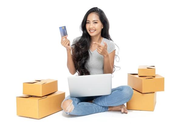Ritratto di una donna asiatica seduta sul pavimento con un sacco di scatole accanto.
