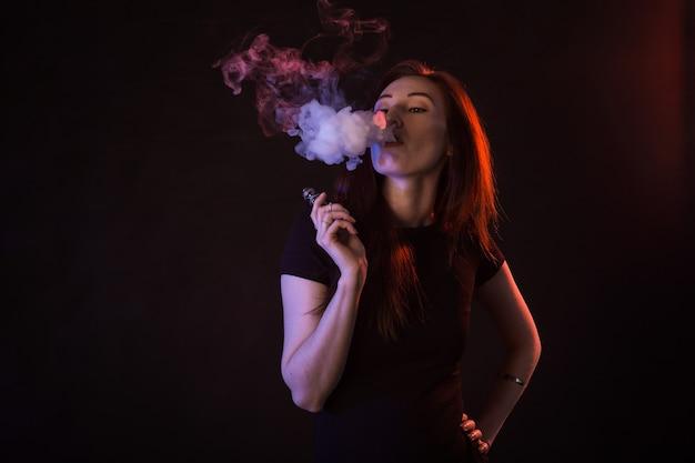 Ritratto di donna asiatica che fuma vape o sigaretta elettronica in luce al neon a sfondo nero.