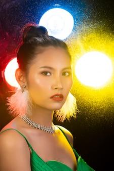 Ritratto di donna asiatica transgender indossa un bellissimo abito lungo da sera verde, sorridi alla telecamera sopra luci posteriori colorate gialle, rosse, sfocate con il fumo e pone look alla moda, illuminazione dello studio copia spazio
