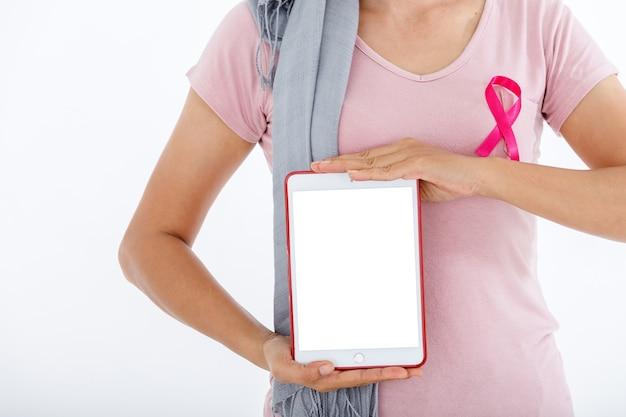 Ritratto di una donna asiatica che utilizza un tablet con uno schermo bianco vuoto dentro con nastro rosa di consapevolezza del cancro al seno isolato su sfondo bianco in bianco copia spazio studio, assistenza sanitaria, concetto di medicina