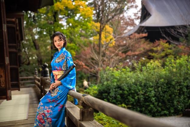 Ritratto della donna asiatica che porta kimono blu giapponese ed ombrello sulla mano della tenuta