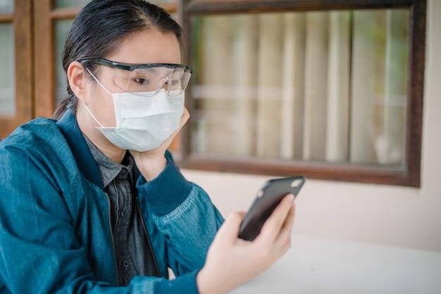 Donna asiatica del ritratto che indossa la maschera protettiva e indossa occhiali trasparenti