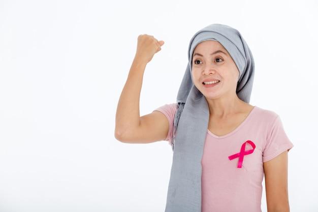 Il ritratto di un malato di cancro mammario di malattia delle donne asiatiche ha espresso fiducia incoraggiarsi in pullover che tiene il nastro rosa isolato su fondo bianco dello studio dello spazio della copia in bianco, concetto della medicina