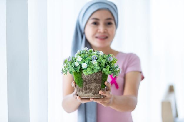 Ritratto di una donna asiatica malata di cancro mammario che tiene vasi di fiori con nastro rosa che indossa il velo dopo il trattamento alla chemioterapia alla finestra nella camera da letto della casa
