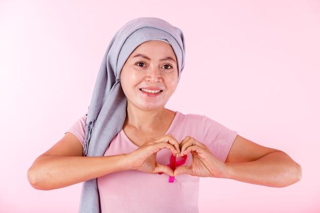 Ritratto di un malato di cancro mammario della malattia delle donne asiatiche nel mostrare il nastro rosa del gesto delle mani a forma di cuore isolato sul fondo dello studio dello spazio della copia in bianco rosa, sanità, concetto della medicina
