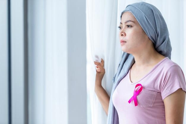 Ritratto di una donna asiatica malata di cancro mammario con nastro rosa che indossa il velo dopo il trattamento alla chemioterapia alla finestra nella camera da letto a casa, assistenza sanitaria, medicina