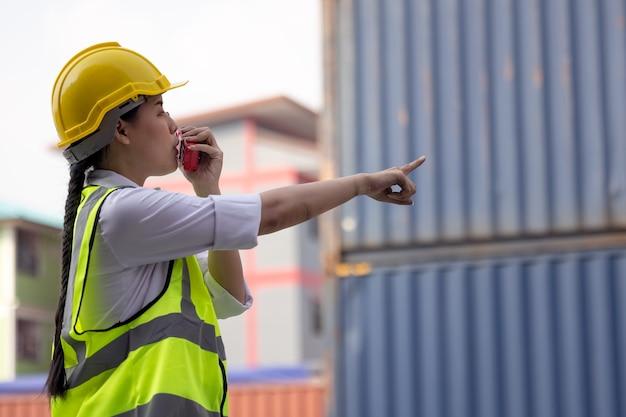 Ritratto della donna asiatica dell'operaio in uniforme di sicurezza che parla con il walkie-talkie per controllare la qualità del lavoro al magazzino del contenitore. lavorando per attività di logistica e spedizioni.