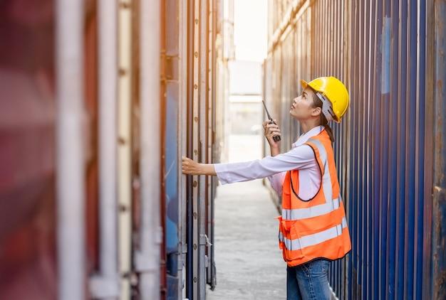 Ritratto lavoratore asiatico donna in uniforme di sicurezza parlando con walkie talkie qualità del lavoro al container